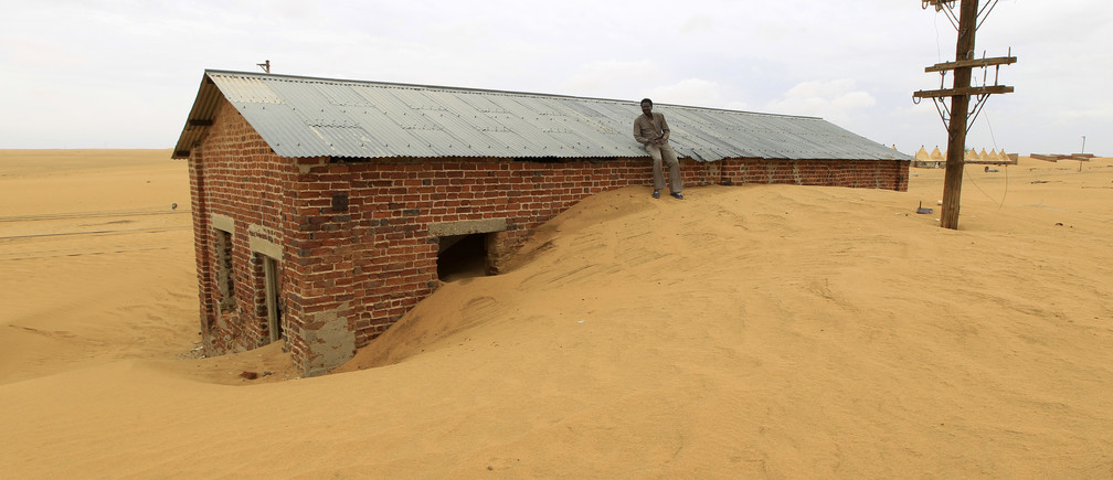 A worker rests on the roof of a building surrounded by sand as a result of desert encroachment at Ogrein Railway Station at the Red Sea State August 1, 2013. REUTERS/ Mohamed Nureldin Abdallah (SUDAN - Tags: ENVIRONMENT SOCIETY TPX IMAGES OF THE DAY) - GM1E9820N8101