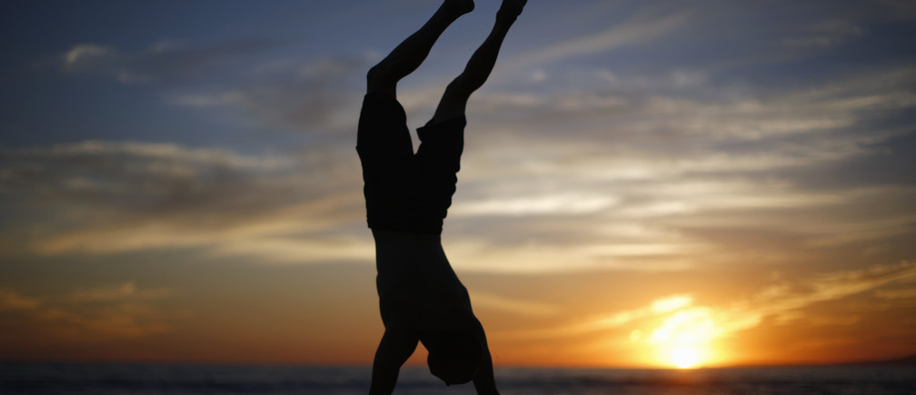 A man does a handstand as the sun sets over the Pacific Ocean on the beach in Santa Monica, California October 3, 2014. Southern California sizzled in a heat wave as temperatures soared above 100 degrees Fahrenheit in parts of Los Angeles.  REUTERS/Lucy Nicholson (UNITED STATES - Tags: ENVIRONMENT SOCIETY) - GM1EAA40UQZ01