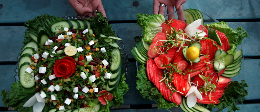 A waiter presents two types of salad served by Habibi restaurant in Peshawar, Pakistan January 31, 2018. REUTERS/Fayaz Aziz - RC11A36ACAB0