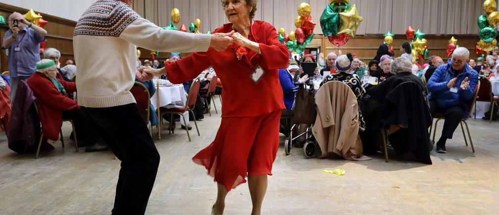 Anita Monk and her neighbour John Everett dance during a Christmas Dinner event for older people at Hammersmith and Fulham Town Hall in London, Britain December 25, 2016. REUTERS/Kevin Coombs - RTX2WFOU