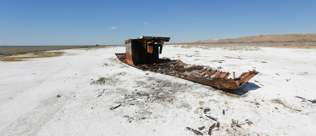 """A ruined ship lays on a salinated part of the Aral Sea coastline near the village of Akespe, south-western Kazakhstan, April 16, 2017. Akespe, home to some 250 people, and Karateren, inhabited by about 150, used to be dominated by fishermen until the water receded too far away - but it is now back in Karateren. REUTERS/Shamil Zhumatov     SEARCH """"ENVIRONMENT ARAL"""" FOR THIS STORY. SEARCH """"WIDER IMAGE"""" FOR ALL STORIES. - RC1EEAC85A10"""