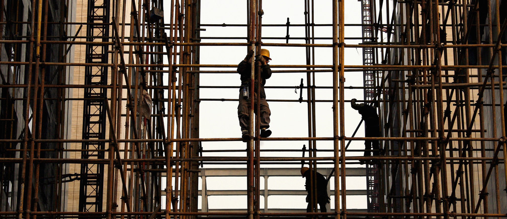 Construction workers stand on scaffolding at a building site in the financial district of Beijing November 18, 2008. China's labour ministry has told local governments not to increase minimum wages in order to avoid putting any additional pressure on companies already feeling the pinch of the global credit crisis, state media said on Monday.     REUTERS/David Gray    (CHINA) - GM1E4BI0ZXH01