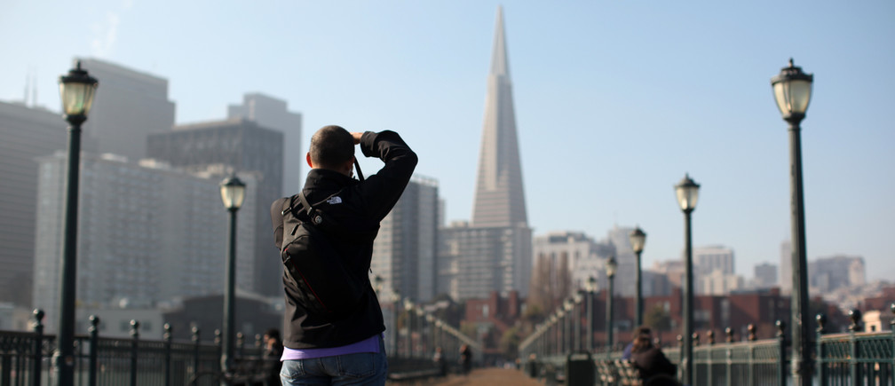 A man photographs the TransAmerica building from Pier 7 in San Francisco, California January 25, 2013.