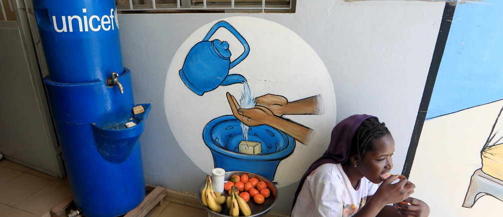 A girl eats as she sits next to a handwashing station, while she sells fruits at the entrance of a medical center in Pikine, on the outskirts of Dakar, Senegal March 9, 2020. Picture taken March 9, 2020. REUTERS/Zohra Bensemra - RC2RLF9CL1JQ