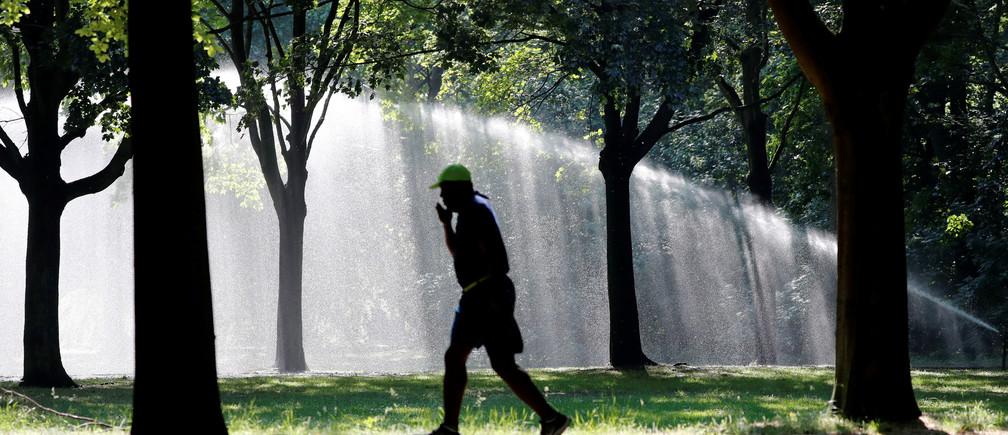 A man jogs across Tiergarten park in Berlin, Germany.