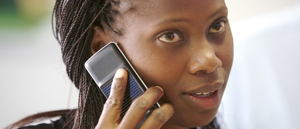 A Safaricom client uses a solar-charged mobile phone handset at a retail centre in Kenya's capital Nairobi, in this September 22, 2009 file photo. Solar cellphones could build on the economic advantages that mobile phones have already brought to far-flung regions of Africa and the Indian subcontinent, including price transparency and more accurate and timely information. Mobile phone penetration in these regions has been held back by a lack of electricity: there is simply no way to charge a cellphone in many rural areas of developing countries. To match feature CELLPHONES-SOLAR/.