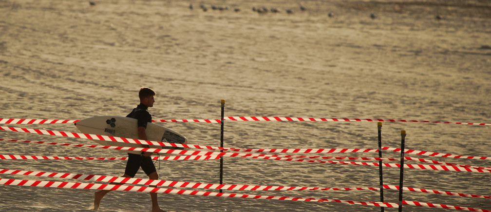 A man walks to the sea as Bondi Beach reopens to surfers and swimmers after it was closed to curb the spread of the coronavirus disease (COVID-19), with strict social distancing measures remaining in place, in Sydney, Australia, April 28, 2020.  REUTERS/Loren Elliott - RC2ADG9UVQ8D
