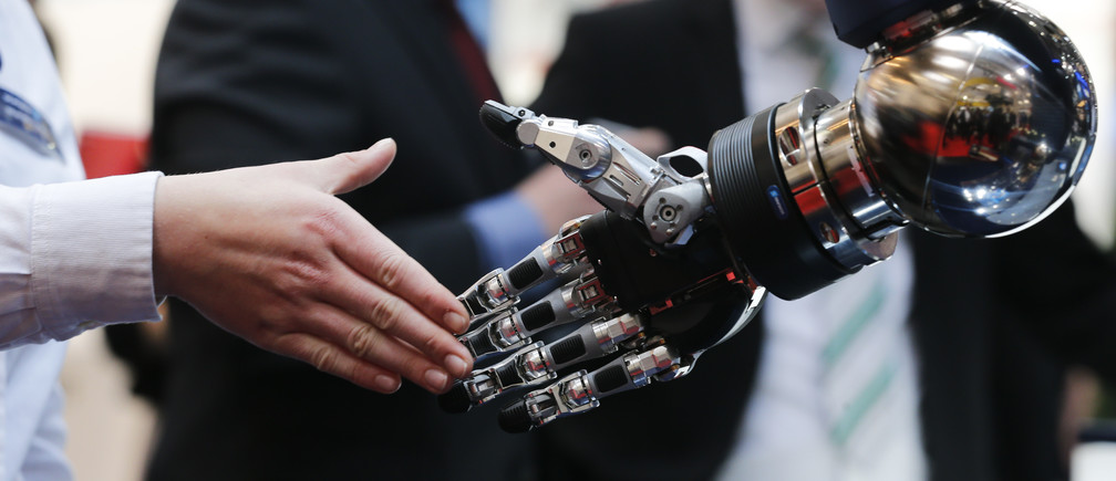 A woman reaches out to shake hands with a robotic hand at the booth of Schunk at the world's largest industrial technology fair, the Hannover Messe, in Hanover April 13, 2015.