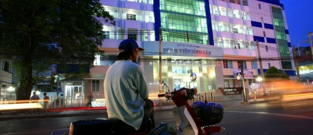 A man sits on his motorbike in front of Binh Dan state hospital in Ho Chi Minh City April 23, 2007. Vietnam is privatizing businesses ranging from banks to energy and telecoms firms into a booming stock market, but a plan for the first flotation of shares in Binh Dan state hospital is deadlocked. REUTERS/Stringer