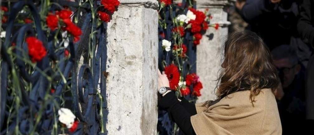 A woman places flowers in front of the Obelisk of Theodosius where Tuesday's suicide bomb attack took place at Sultanahmet square in Istanbul, Turkey January 14, 2016.