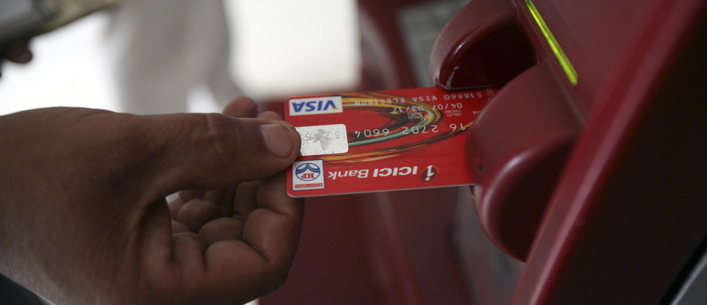 A customer uses his card to withdraw money from an ATM in Jammu October 14, 2008