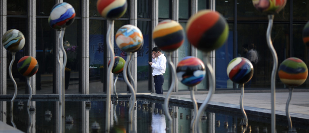 A man uses his mobile phone next an installation in a fountain at a financial district in Beijing October 21, 2014.