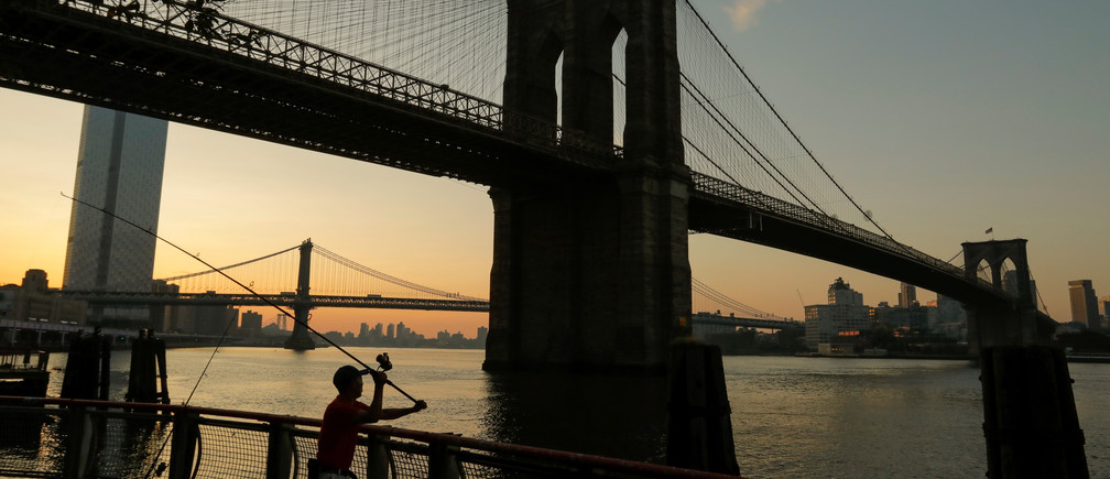 A man casts his line out as he goes fishing under the Brooklyn Bridge at sunrise as a heatwave continues to affect the region in New York, U.S., July 21, 2019. REUTERS/Andrew Kelly     TPX IMAGES OF THE DAY - RC159D8AFC50