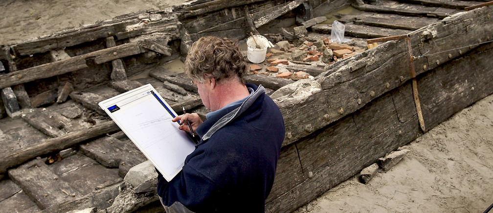 Dutch ship archeologist Jaap Morel sketches the ancient Roman Bargewhich was dug up in the town of Woerden in the centre of theNetherlands October 21, 2003. The barge, dating from around 100 AD, wasdug up in the centre of the Dutch town which was once the location ofthe Roman military settlement Castellum Laurium and a trading outposton the banks of the Rhine. Archaeologists said on Tuesday the ship,equipped with oars, was a unique find that explains how imperial Romedefended itself on its Northern frontiers. REUTERS/Michael KoorenMKN/CRB - RP4DRHYAHFAB
