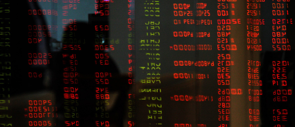 A Filipino trader stands against the reflections of trading figures inside the Philippine Stock Exchange in Makati's financial district at Manila February 27, 2006. REUTERS/Romeo Ranoco - RP3DSFDDHDAA