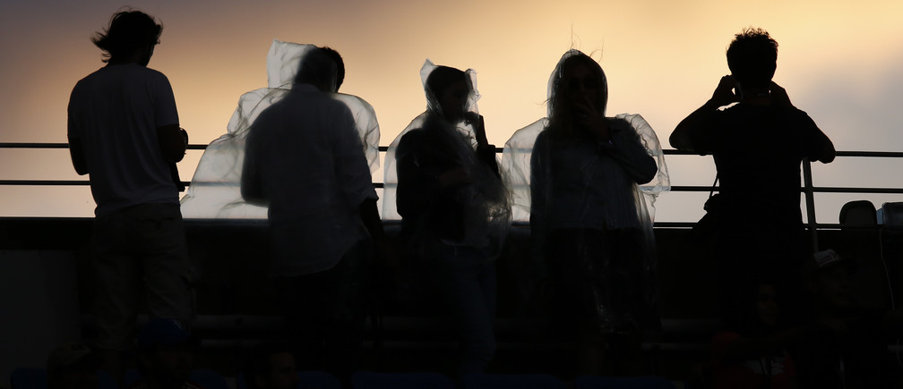 Fans wearing rain ponchos are backlit as they watch the sunset from Arthur Ashe Stadium ahead of the mens final between Roger Federer of Switzerland and Novak Djokovic of Serbia at the U.S. Open Championships tennis tournament in New York, September 13, 2015. REUTERS/Carlo Allegri  - TB3EB9E00WFLJ