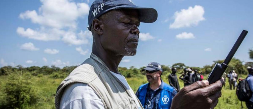 A World Food Programme employee uses a satellite phone to coordinate a U.N's World Food Programme (WFP) food aid air drop near the town of Katdalok, in Jonglei State of South Sudan July 30, 2018.