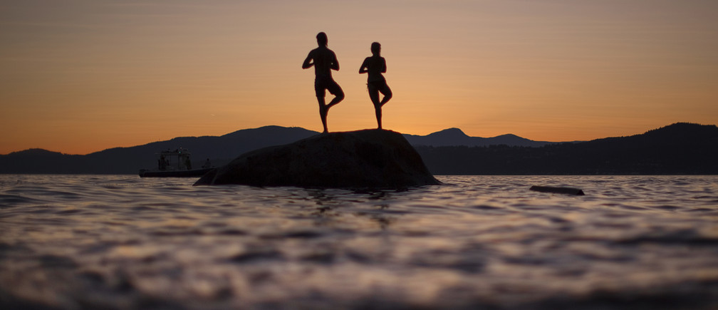 A couple stand on a rock facing the sunset along the shores of English Bay in Vancouver, British Columbia July 23, 2013. REUTERS/Andy Clark (CANADA - Tags: SOCIETY) - GM1E97O114A01