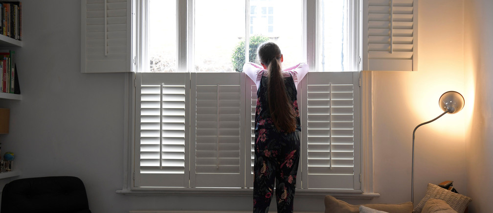 Nine-year-old Eve looks out of the front window at home, as the number of coronavirus disease (COVID-19) cases grow around the world, in London, Britain, March 17, 2020. REUTERS/Toby Melville - RC2CSF9D6SUC