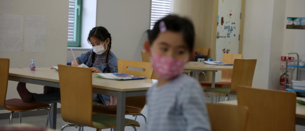 "A child, wearing a protective face mask, following an outbreak of coronavirus, is seen at ""Stella Kids"", daycare center in Tokyo, Japan, March 5, 2020."