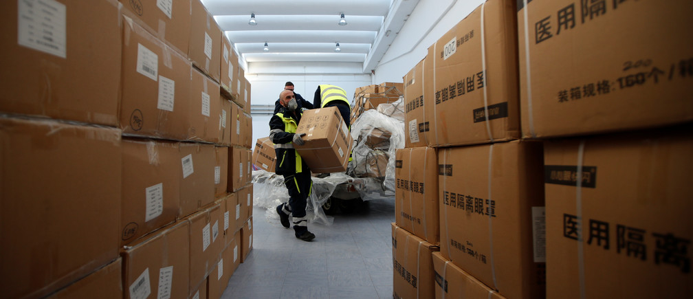 Workers pile up a shipment containing supplies of personal protective equipment (PPE) at Bari airport after arriving from Guangzhou, China, to help the southern Italian region of Puglia combat a spread of the coronavirus disease (COVID-19), in Bari, Italy, April 7, 2020.