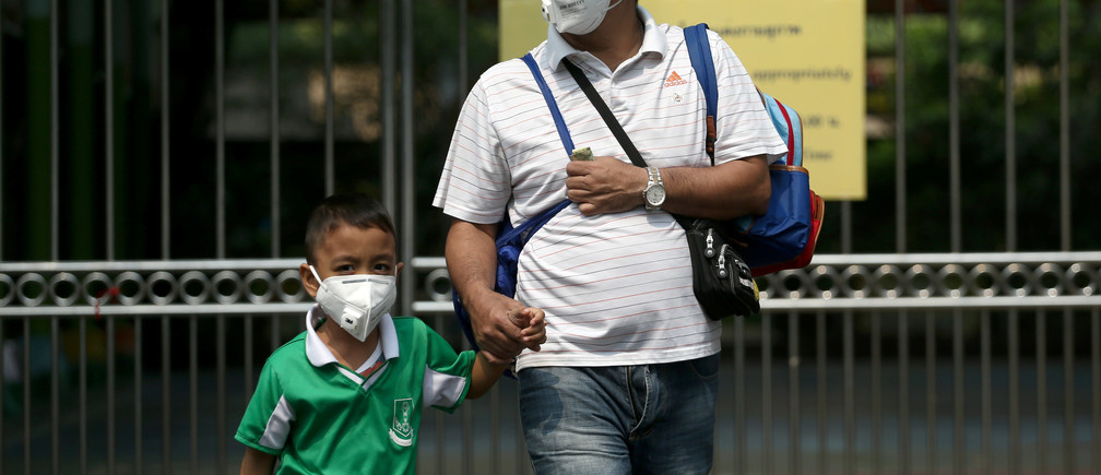 A student and his father wear masks outside a public school, as classes in over 400 Bangkok schools have been cancelled due to worsening air pollution, in Bangkok, Thailand, January 30, 2019. REUTERS/Athit Perawongmetha - RC1E79158500
