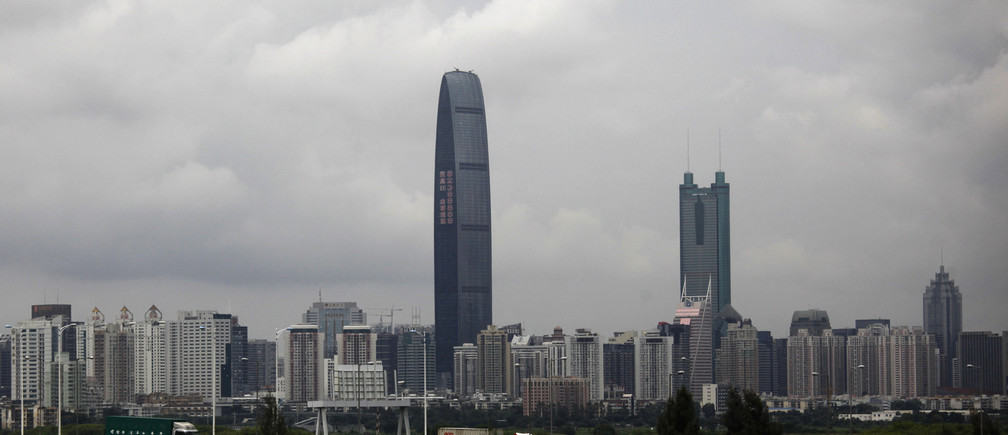 Container trucks cross a bridge in front of the 100-floor Kingkey 100, the tallest building in downtown Shenzhen neighboring Hong Kong, May 16, 2012.  REUTERS/Bobby Yip (CHINA - Tags: BUSINESS) - GM1E85G1I1801