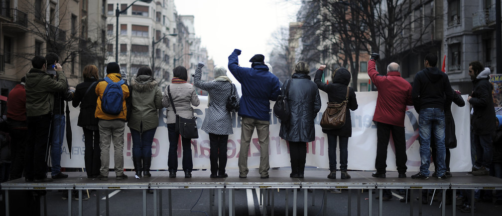 "Members of public sector unions raise their fists as they sing ""L'Internationale"" during a march in central Bilbao February 9, 2012."