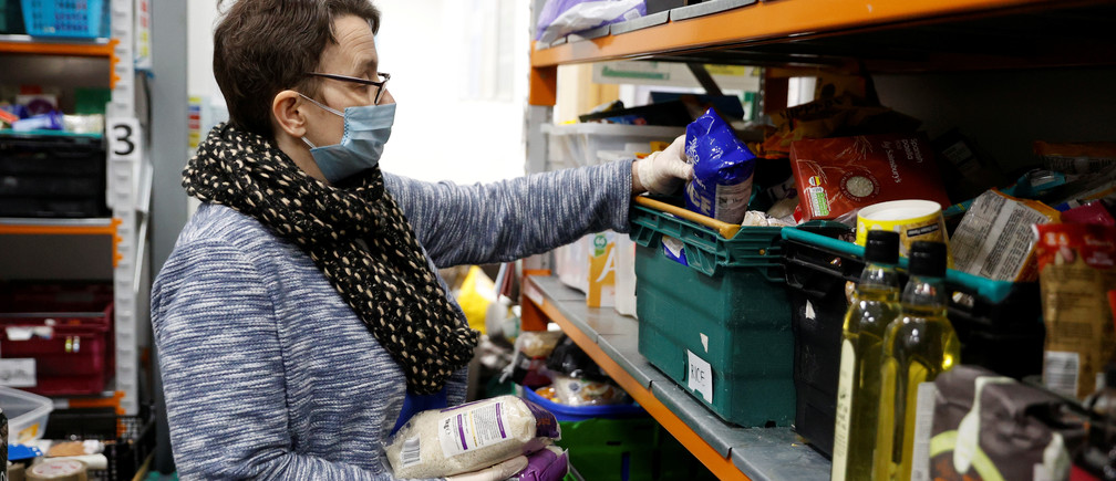 A volunteer at the North Enfield Foodbank Charity packs a bag of groceries and other household items for distribution in Enfield as the spread of coronavirus disease (COVID-19) continues in London, Britain March 24, 2020.