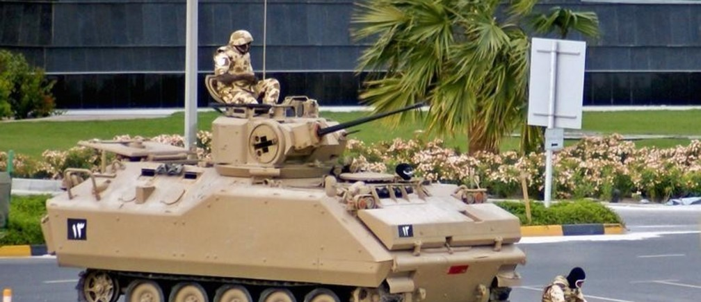A soldier from the Gulf Cooperation Council (GCC) forces prays in front of his Armour Personnel Carrier as his fellow solider keeps watch while they guard the Bahrain Financial Harbour in Manama March 16, 2011. Bahraini forces used tanks and helicopters to drive protesters from the streets on Wednesday clearing a camp that had become a symbol of the Shi'ite Muslim uprising and drawing rare criticism from their U.S. Allies.