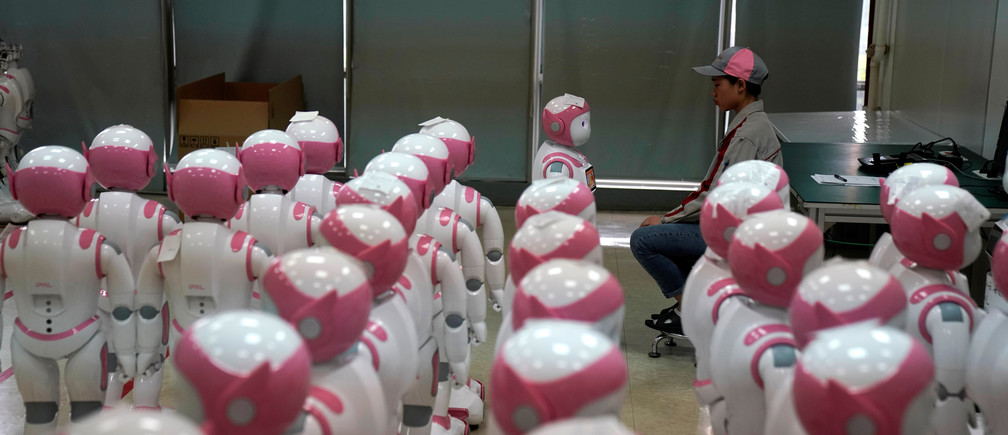 A worker puts finishing touches to an iPal social robot, designed by AvatarMind, at an assembly plant in Suzhou, Jiangsu province, China July 4, 2018. Designed to offer education, care and companionship to children and the elderly, the 3.5-feet tall humanoid robots come in two genders and can tell stories, take photos and deliver educational or promotional content. Picture taken July 4, 2018.REUTERS/Aly Song - RC12AA5524B0