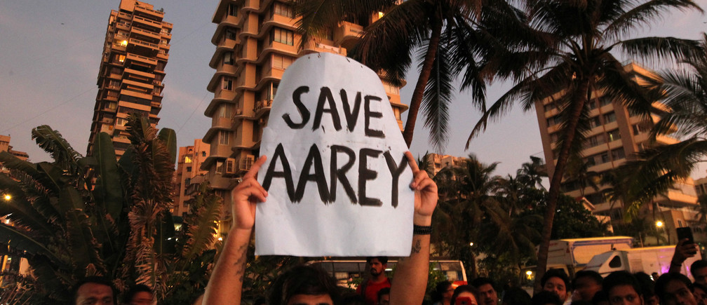 A man displays a placard at a promenade during a protest demanding that the Mumbai Metro Rail Corp Ltd (MMRCL) not cut trees to build a train parking shed for an upcoming subway line, in Mumbai, India, October 6, 2019.  REUTERS/Prashant Waydande - RC178F590A70