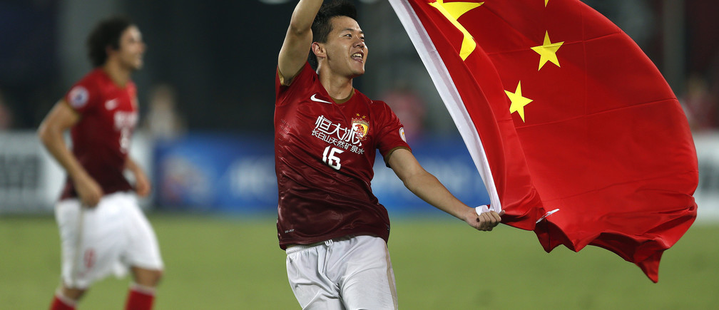 Huang Bowen (16) of China's Guangzhou Evergrande celebrates with the Chinese national flag after winning the team's final match of the AFC Champions' League against South Korea's FC Seoul at Tianhe stadium in the southern Chinese city of Guangzhou November 9, 2013.