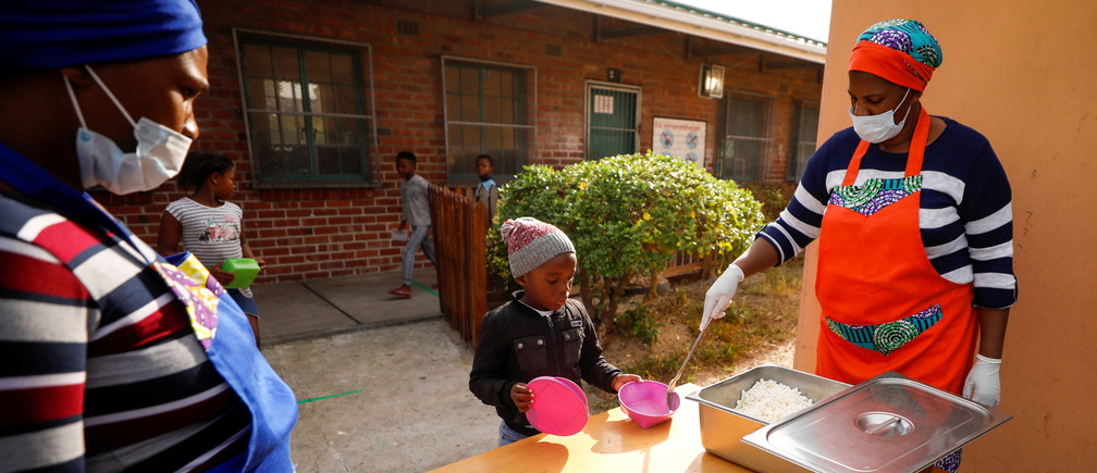 Volunteers serve food at a school feeding scheme in Gugulethu townshi, Cape Town, South Africa.