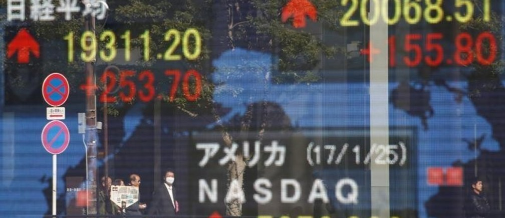 Pedestrians are reflected on an electronic board showing Japan's Nikkei average (top L), the Dow Jones average (top R) and the stock averages of other countries outside a brokerage in Tokyo, Japan, January 26, 2017.  REUTERS/Kim Kyung-Hoon - RTSXE6U
