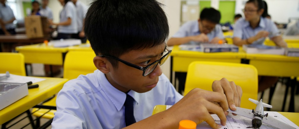 A student assembles a model aeroplane during an enrichment class at a secondary school in Singapore October 27, 2016.