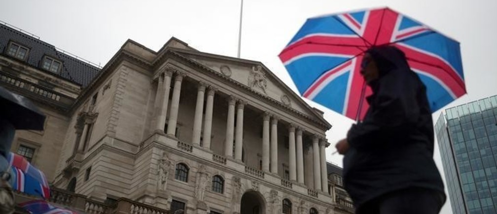 A pedestrian shelters under a Union Flag umbrella in front of the Bank of England, in London, Britain August 16, 2018.  REUTERS/ Hannah McKay