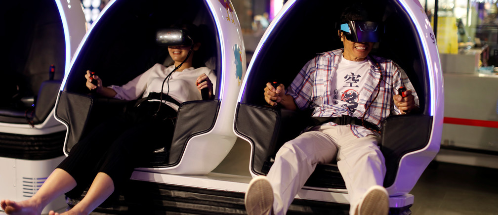 People try a VR Cinema simulator at a shopping mall in Bangkok, Thailand September 20, 2018. REUTERS/Jorge Silva - RC1894F92770