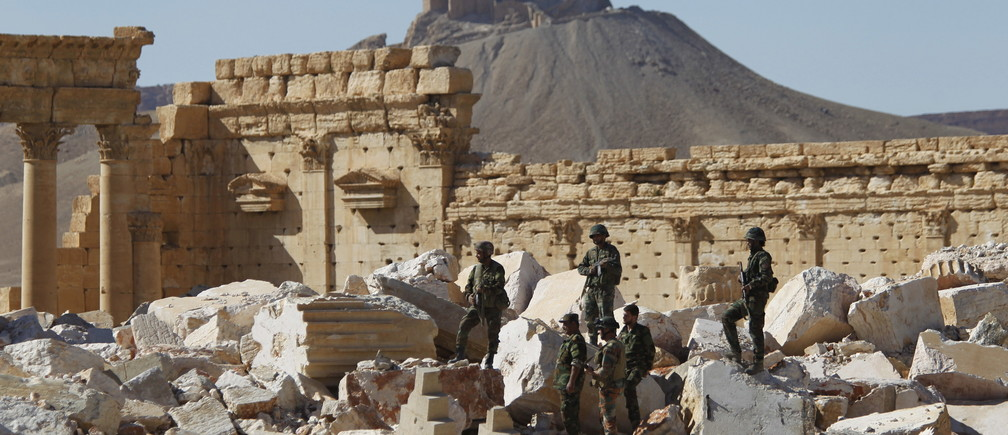Syrian army soldiers stands on the ruins of the Temple of Bel in the historic city of Palmyra, in Homs Governorate, Syria in this April 1, 2016 file photo. The Fakhreddin's Castle is seen in the background. REUTERS/Omar Sanadiki/Files          TPX IMAGES OF THE DAY      - GF10000368972