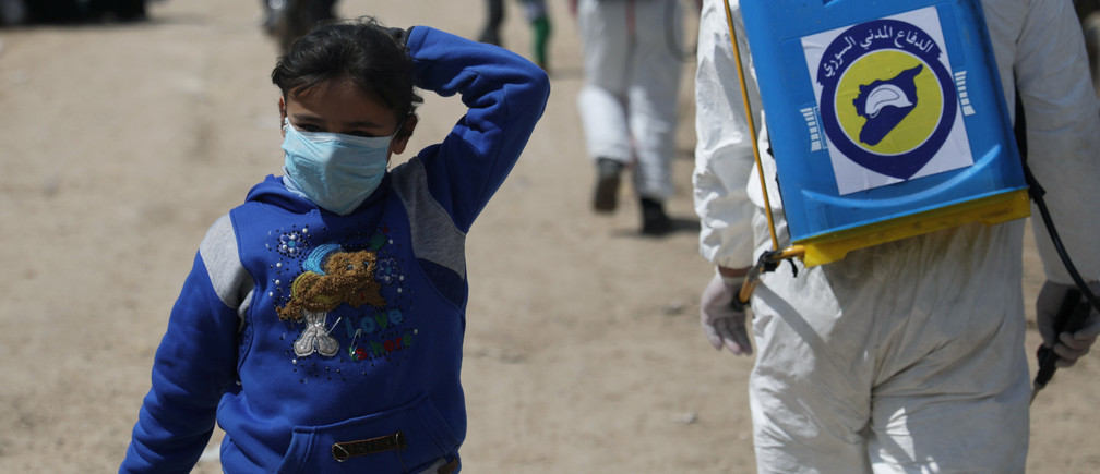An internally displaced Syrian girl wears a face mask as members of the Syrian Civil defence sanitize the Bab Al-Nour internally displaced persons camp, to prevent the spread of coronavirus disease (COVID-19) in Azaz, Syria March 26, 2020. REUTERS/Khalil Ashawi - RC2TRF9JPD9I