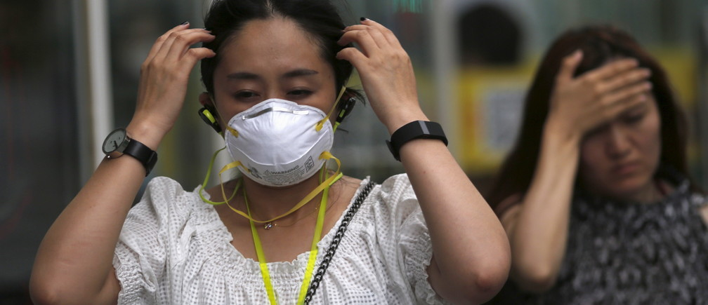 A woman wearing a mask makes her way at a business district during a polluted day in Beijing, China, June 29, 2015.