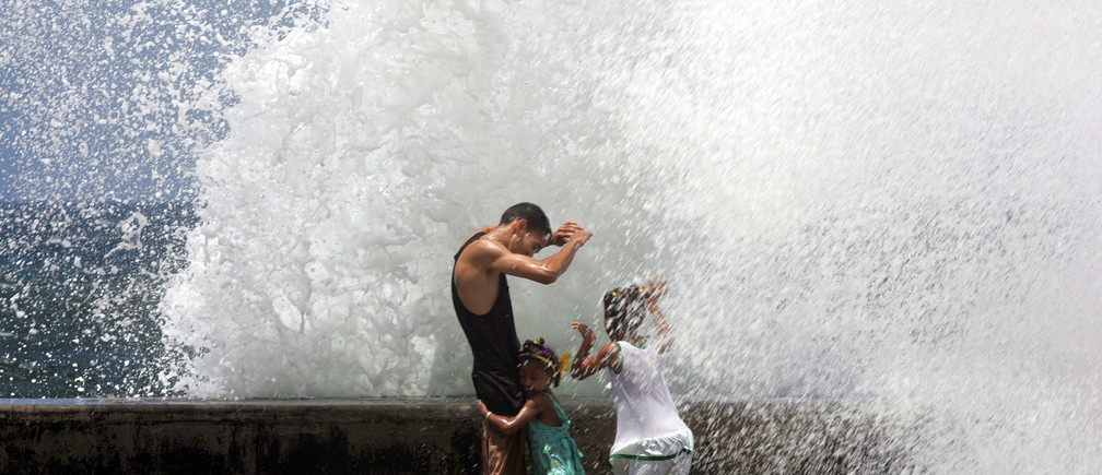 A Cuban father and his two daughters enjoy the waves battering against Havana's seafront El Malecon, September 5, 2004. Hurricane Frances caused high waves and strong winds in the Cuban capital before being downgraded as a tropical storm over Florida. REUTERS/Claudia Daut NO RIGHTS CLEARANCES OR PERMISSIONS ARE REQUIRED FOR THIS IMAGE  CD - RP5DRHXRZLAC