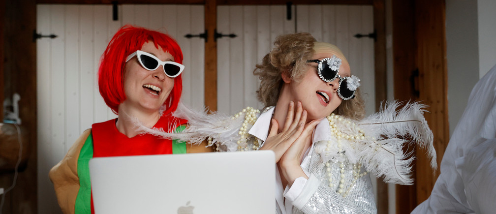 Emily dressed as Elton John and Molly as Lady Gaga watch the concert One World: Together At Home, as the spread of the coronavirus disease (COVID-19) continues, Henton, Britain, April 18, 2020. REUTERS/Eddie Keogh - RC267G95RC62