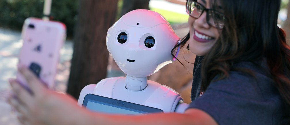 "A student takes a selfie with ""Pepper"", a humanoid robot programmed as a student assistant"