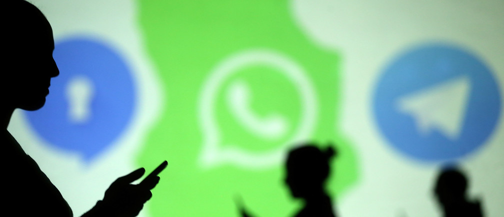 Silhouettes of mobile users are seen next to logos of social media apps Signal, Whatsapp and Telegram projected on a screen in this picture illustration taken March 28, 2018.  REUTERS/Dado Ruvic/Illustration