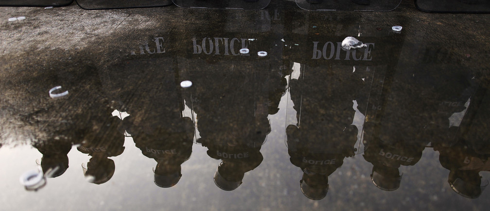 Thai riot policemen are reflected in water behind their shields as they take a part in an exercise in an army base in Bangkok's suburbs February 20, 2010. Thai security forces, army and police organized a joint exercise to prepare for possible anti-government protests in the country.  REUTERS/Damir Sagolj (THAILAND - Tags: POLITICS CIVIL UNREST MILITARY) - GM1E62K1HUZ01