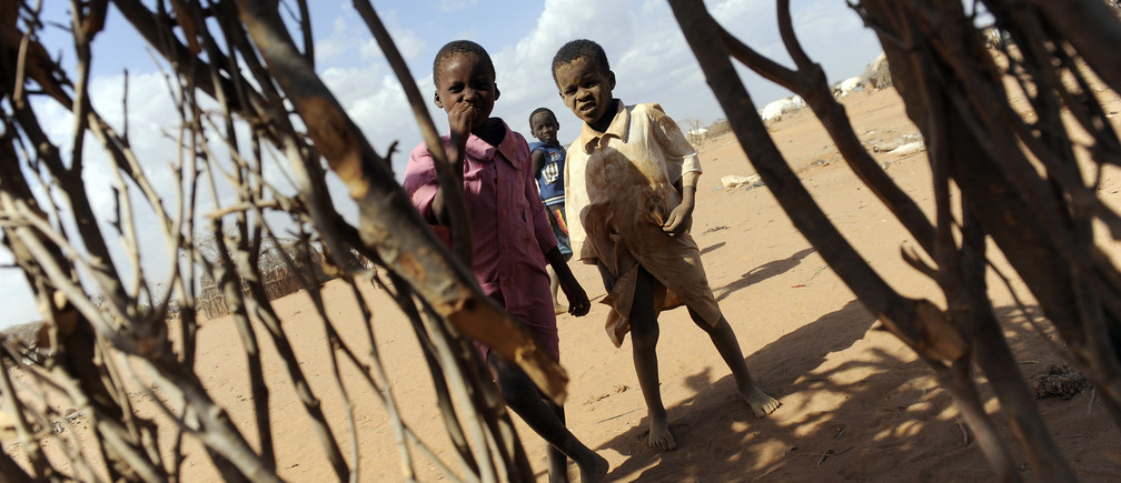 "Children play outside the shell of a makeshift home, or ""tukul"", in the outskirts of Dagahaley settlement at Kenya's Dadaab Refugee Camp, situated northeast of the capital Nairobi, near the Somali border, August 31, 2011."
