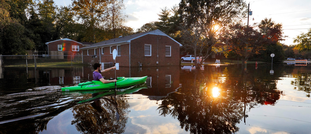 A resident paddles his kayak out of his neighborhood after checking the condition of his house as river levels rise into town in the aftermath of Hurricane Matthew, in Greenville, North Carolina, U.S. October 14, 2016.