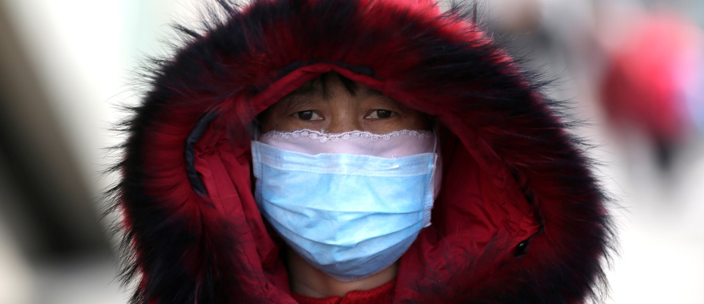 A woman wearing a mask is seen upon her arrival at Beijing West Railway Station in Beijing, China, as the country is hit by an outbreak of the new coronavirus, January 30, 2020. Picture taken January 30, 2020. REUTERS/Jason Lee - RC29SE9MADDC