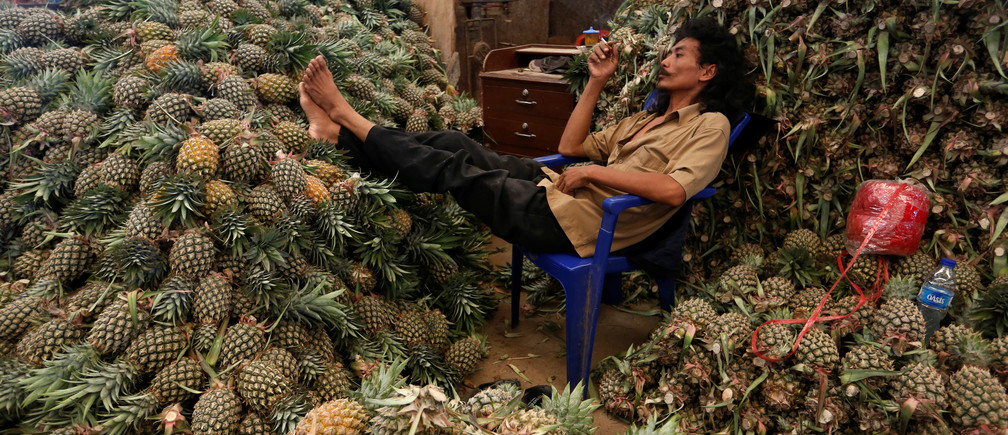 A worker rests beside piles of pineapple at the Kramat Jati wholesale market in Jakarta, Indonesia May 1, 2018. Picture taken May 1, 2018. REUTERS/Willy Kurniawan